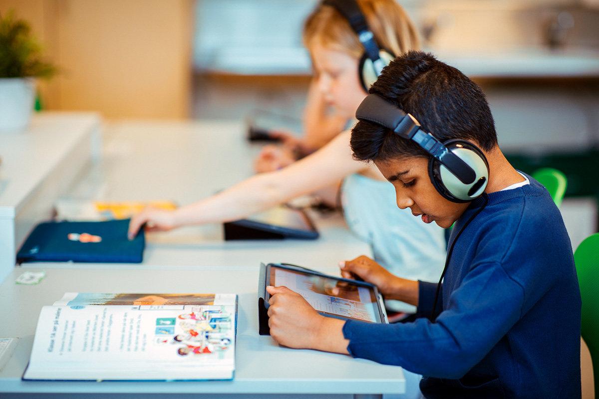 Bilde av en gutt med bok og skjerm